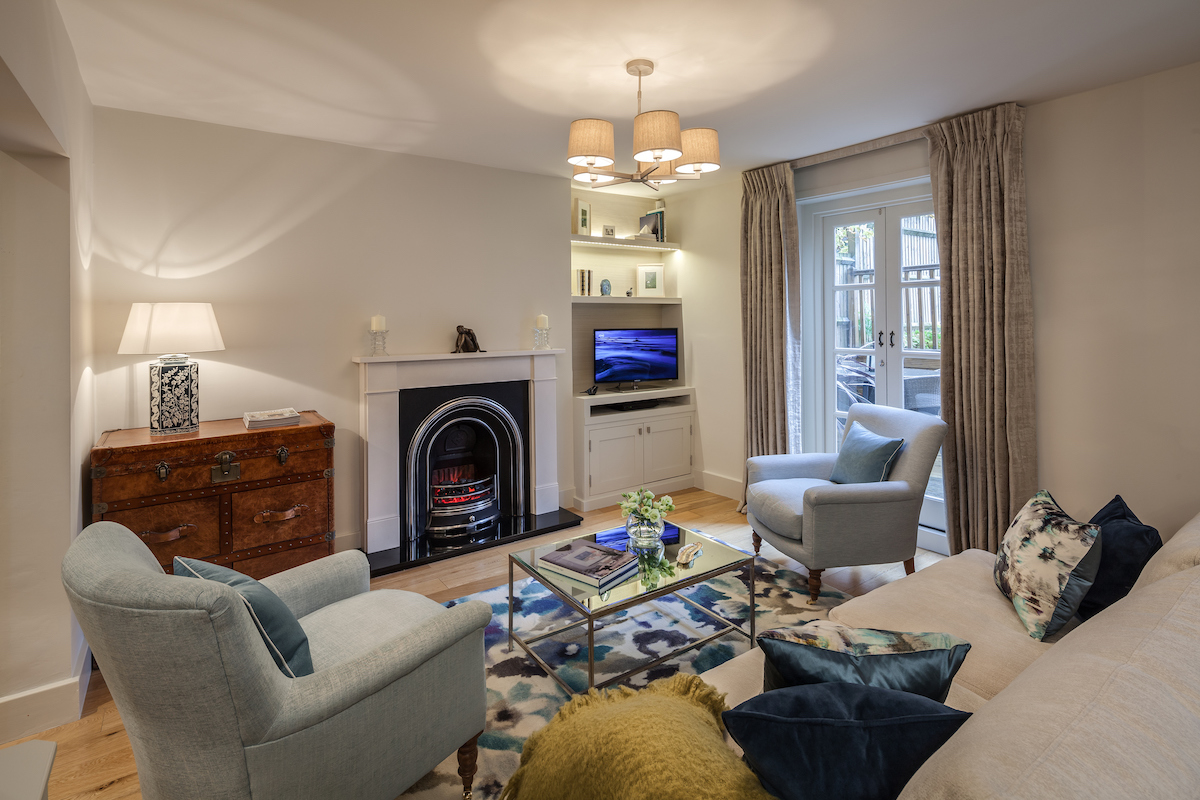 London interior design: Sitting room in a victorian basement flat with neutral tones and bright accents of blue.